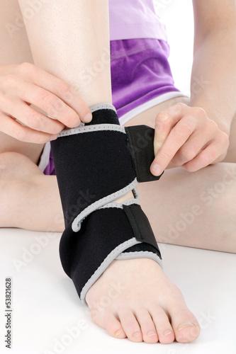 Junge Sportlerin bandagiert Fuß