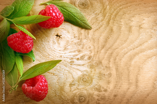 Ripe red raspberries on a woodgrain texture