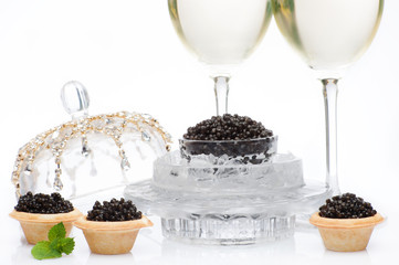 Black caviar and champagne in glass on a white