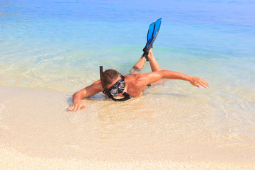 Happy man with snorkeling gears on the beach