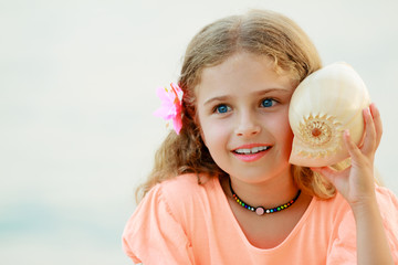 Listening to the sea - Lovely girl with shell at the beach