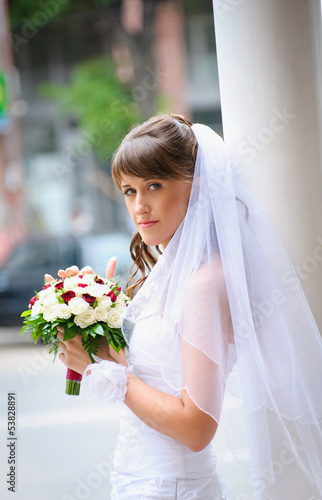 pensive bride in white dress standing and holding roses bouquet