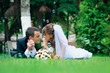 groom and bride lie on a grass around soap bubbles