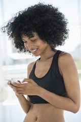 Smiling woman text messaging on a mobile phone