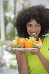 Portrait of a smiling woman holding a plate of fruits