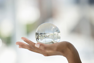 Close-up of a person's hand holding a crystal ball