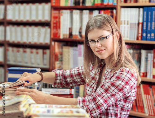 Female owner of book shop or library putting books in order.