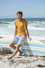 Man sitting on a surfboard on the beach