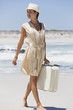 Beautiful woman carrying a suitcase on the beach
