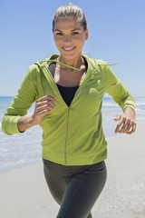 Smiling woman running on the beach