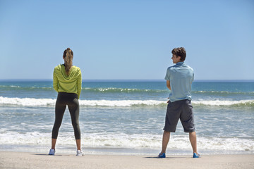 Rear view of a woman and her coach exercising on the beach