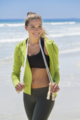 Woman holding a skipping rope on the beach