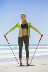 Smiling woman exercising with a chest expander on the beach