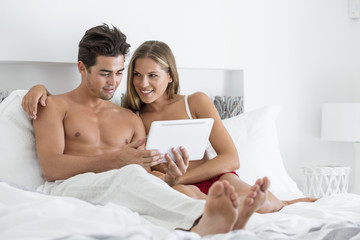 Couple reading a digital tablet in the bed