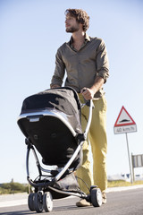Man pushing a baby stroller
