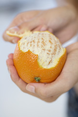 Close-up of a woman's hand peeling an orange