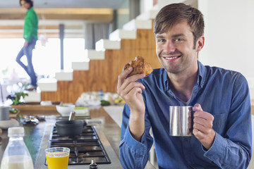 Man having breakfast at a kitchen counter with his wife in the background