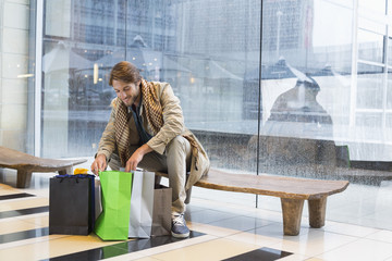 Man sitting at an airport lounge looking at shopping bags