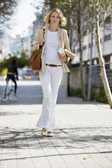 Female architect walking on a street with paper rolls