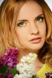 Portrait of a young beautiful girl with lilac flowers
