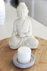 Close-up of a Buddha statue with a candle on a table