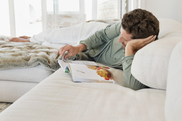 Man lying on the bed and reading a magazine