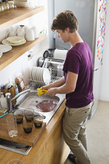 Man washing dishes in his kitchen