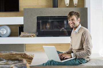 Portrait of a smiling man using a laptop