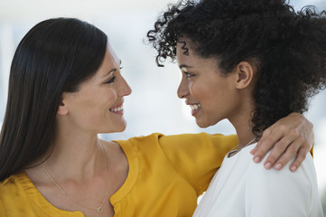 Close-up of two female friends smiling at each other