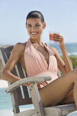 Beautiful woman holding a glass of juice and sitting on a chair on the beach