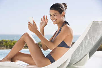 Beautiful woman video calling on cell phone while sunbathing on the beach