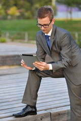 Businessman using electronic tablet outside in a park