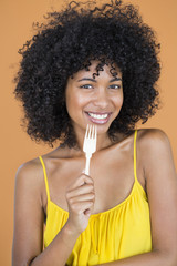 Portrait of a woman holding a fork and smiling