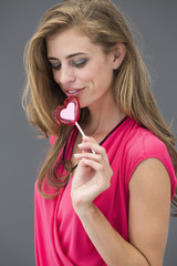 Woman eating a heart shape lollipop