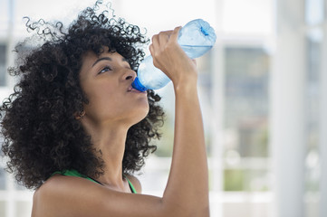 Close-up of a woman drinking water from a bottle
