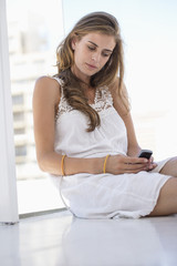 Woman sitting on the floor and using a mobile phone