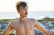 Shirtless man yawning with arm outstretched on the beach