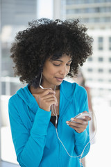 Smiling woman listening to music on a mobile phone