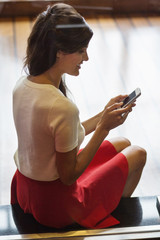 Woman text messaging on a mobile phone and smiling