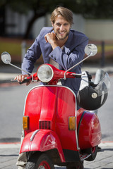 Portrait of a man sitting on a scooter and smiling