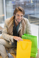 Portrait of a smiling man sitting at an airport lounge with shopping bags