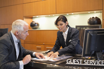 Receptionist showing a brochure to a businessman at a hotel reception counter