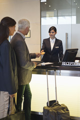 Business couple paying with a credit card at the hotel reception counter