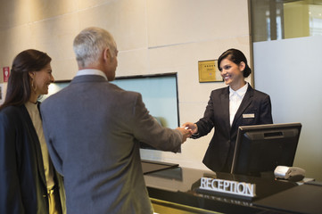 Business couple getting key card at the hotel reception counter