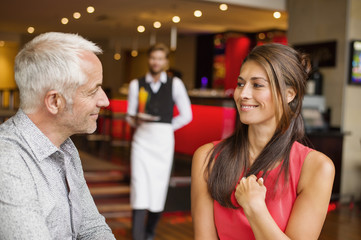 Couple smiling in a restaurant with waiter in the background