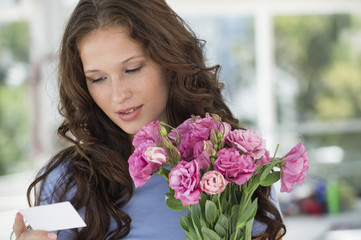 Woman reading a card with bouquet of flowers