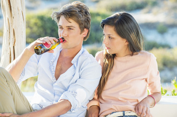 Couple enjoying beer outdoors on a vacation