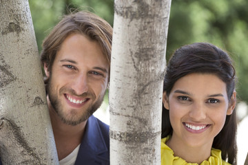 Portrait of a couple smiling behind a tree