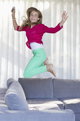 Portrait of a smiling girl jumping on a couch