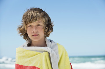 Portrait of a boy wrapped in a towel on the beach
